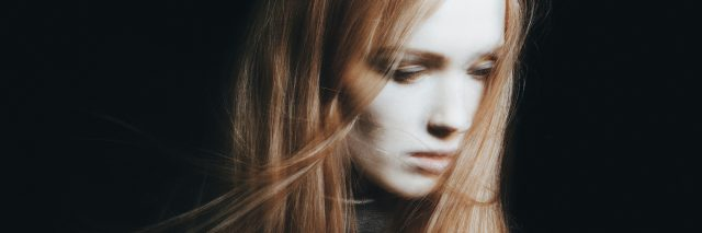 blurred photo of a woman with long red hair looking down and away