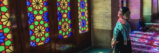 Woman looking at a stained glass window