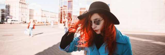 Woman with red curly hair in blue coat and black round sunglasses in city.