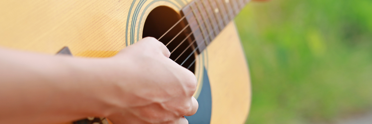 Hand playing acoustic guitar.