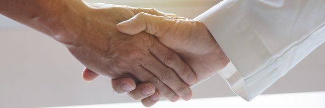 A photo of a male doctor's hand shaking another man's hand.