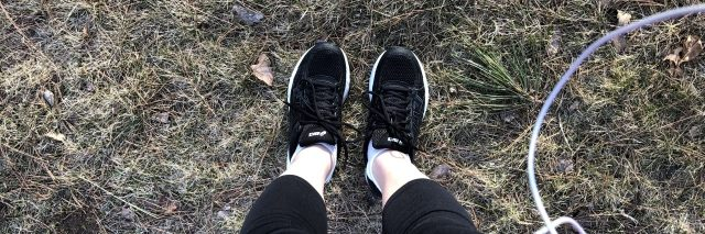 woman standing outside in her running shoes