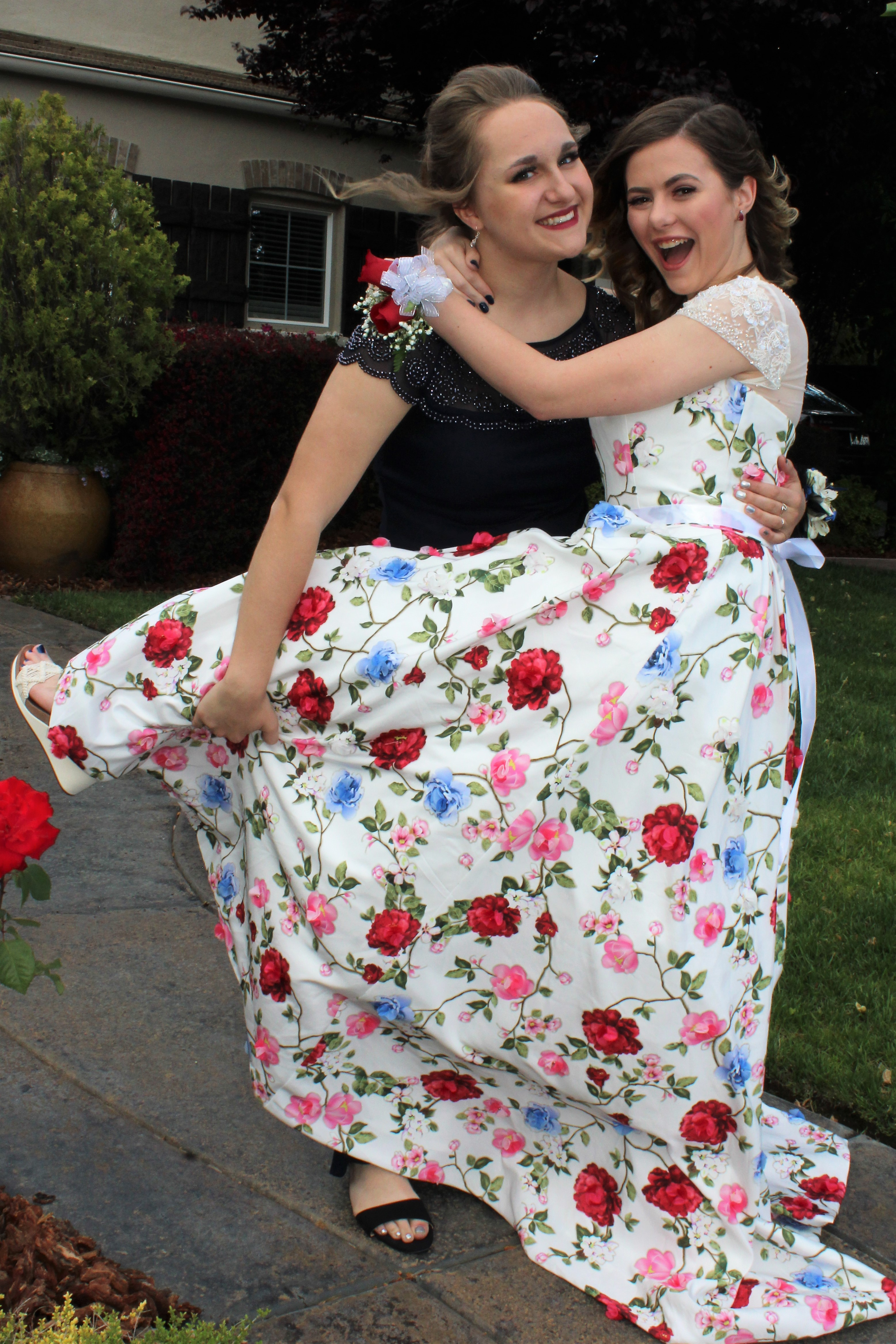 The writer and her friend posing in their prom dresses.