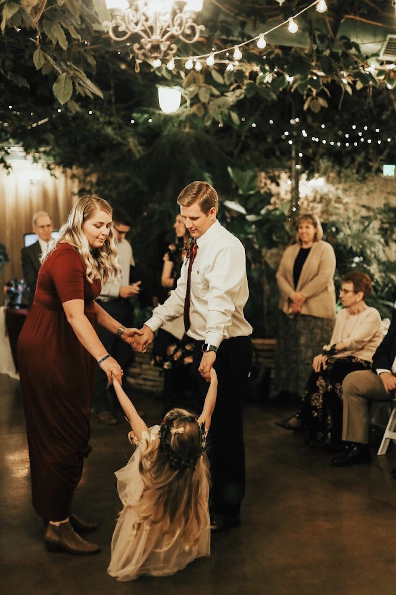 A photo of the writer dancing with a man and a child at a wedding.