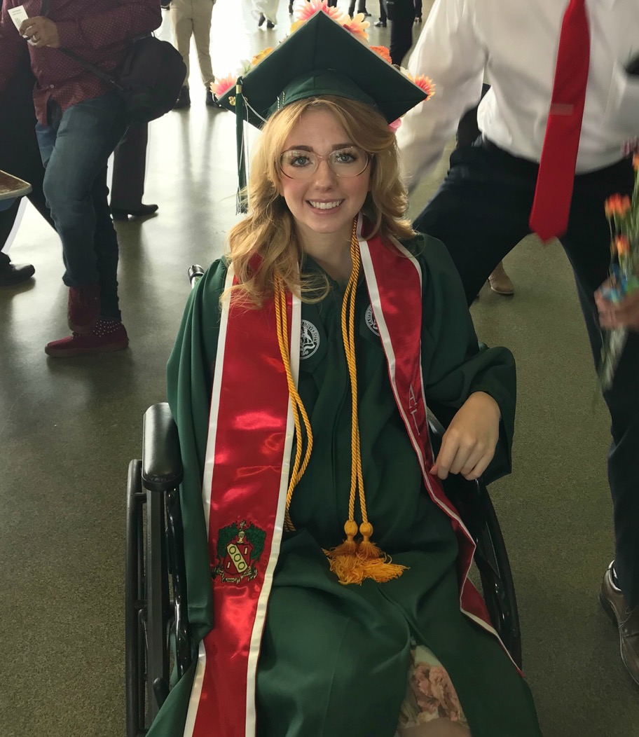 The writer sitting in her wheel chair on graduation day.