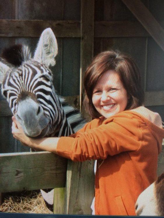 Joanne smiling next to a zebra