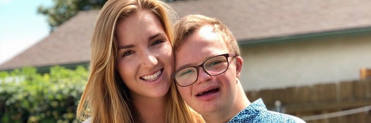 Image of Julia with twin brother Michael who has Down syndrome.They are huggig and holding hands smiling at camera.