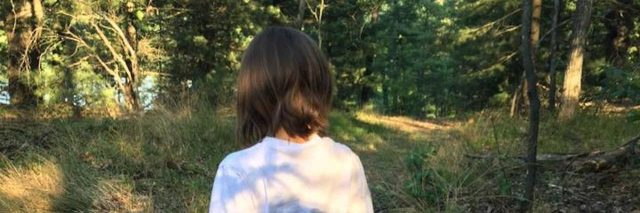 Back of girl, she is wearing a white shirt and jeans, walking in the woods