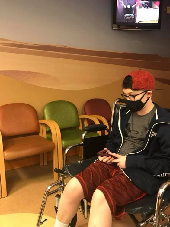 Meg's son, wearing a medical mask and sitting in a wheelchair in the waiting room