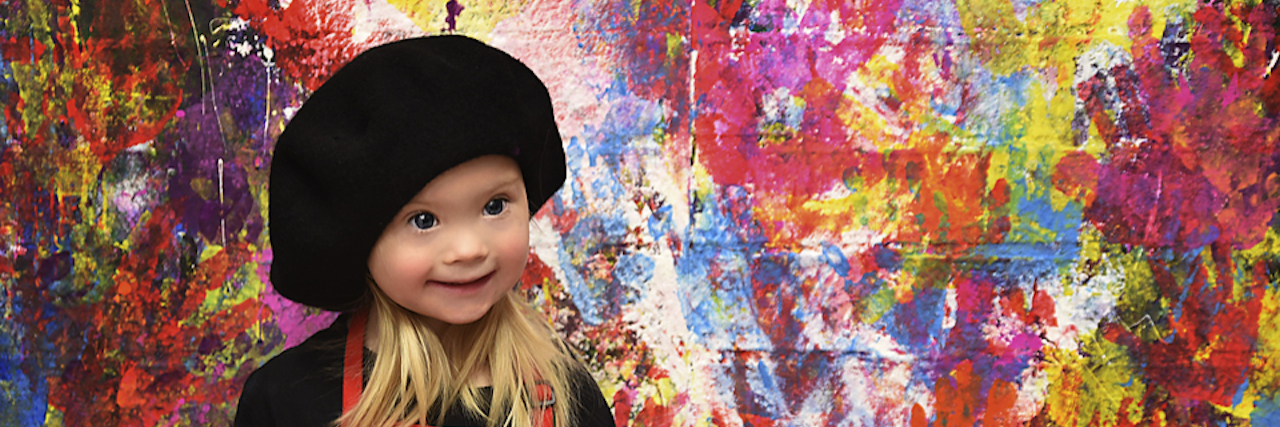 Girl with Down syndrome dressed as artist wearing red apron and the wall behing is colored in hand prints of different colors, no white spaces.