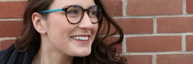 image of young woman smiling against brick wall with name overlaid