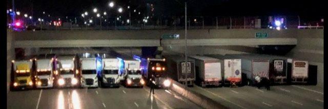 Semi-trucks under a bridge