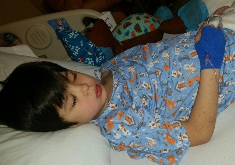 Valerie's son laying in a hospital bed