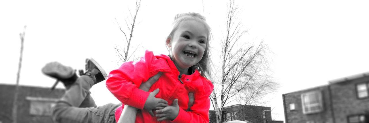Black and white image of dad lifting daughter ith Down syndrome in the sky, her coat is red, only color in the image