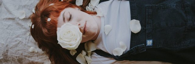 woman with tattoos laying on bed with flowers around her