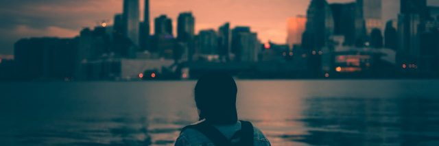 young woman wearing backpack looking at Toronto skyline at sunset