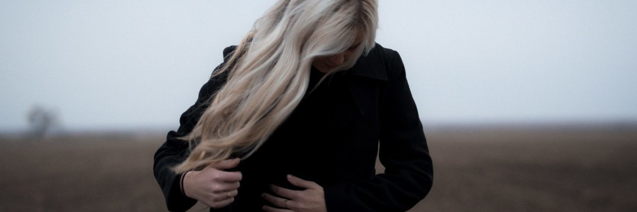 blonde woman wearing black coat and looking away from camera