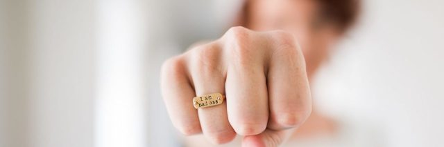 woman with fist towards camera showing ring that says I am badass