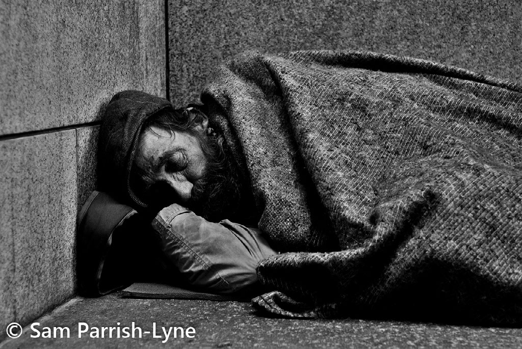 Homeless man lying on the street, photo by Sam Parrish-Lyne.