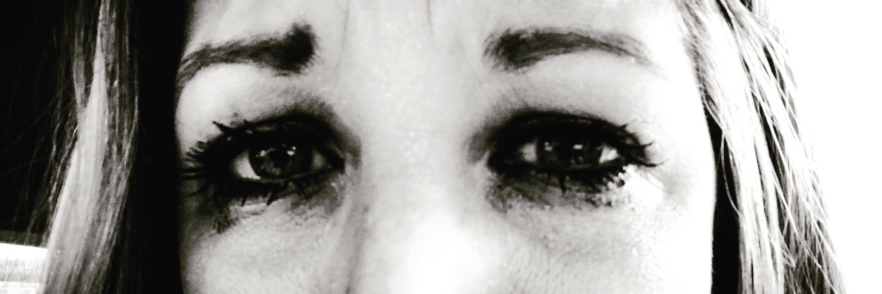Black and white close up of woman's eyes with tears