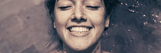 Woman lying in ocean and smiling close up