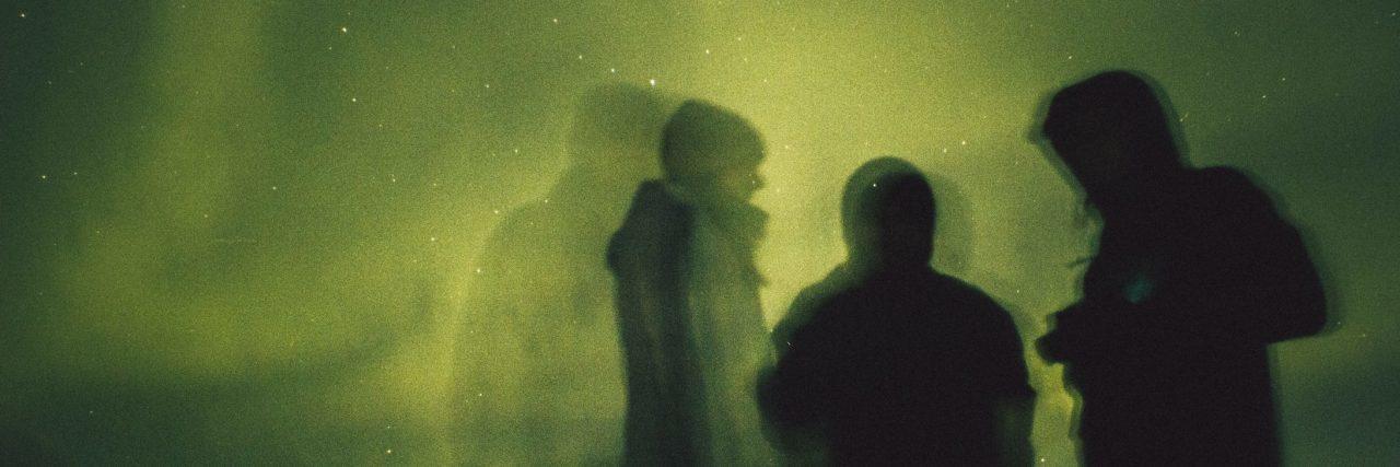 three people framed against green aurora borealis northern lights