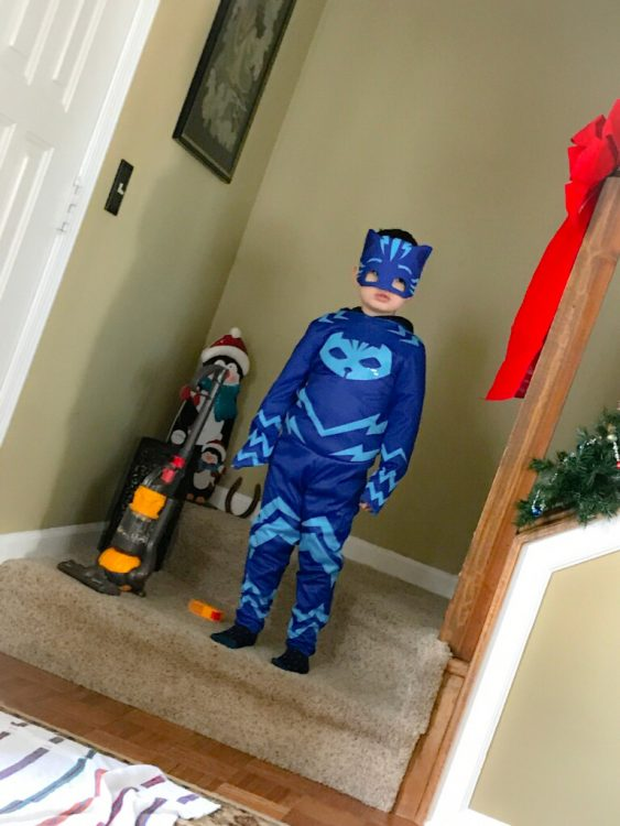 child wearing blue superhero outfit and posing by a vacuum cleaner