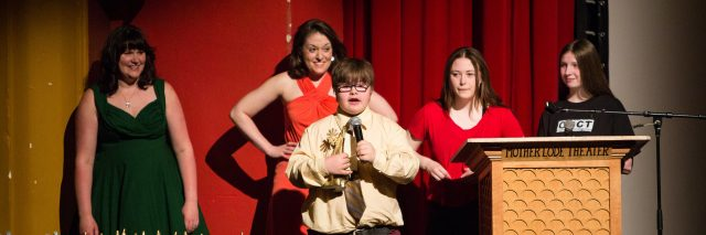 Boy with Down syndrome speaking into microphone, four teenagers stand behind him, there is a table with trophies