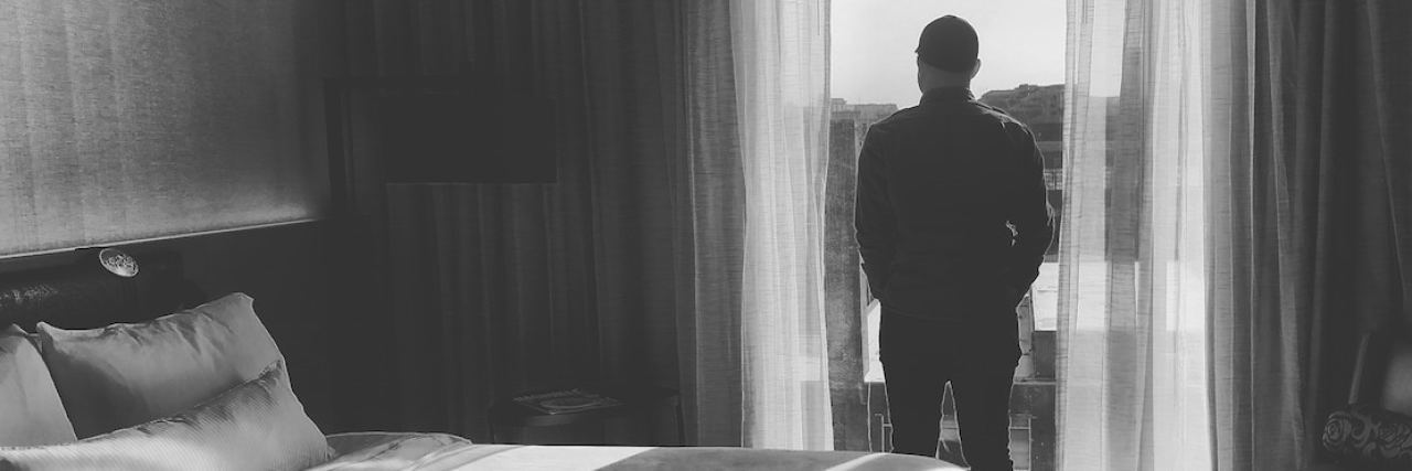 A man standing in his bedroom looking out the window