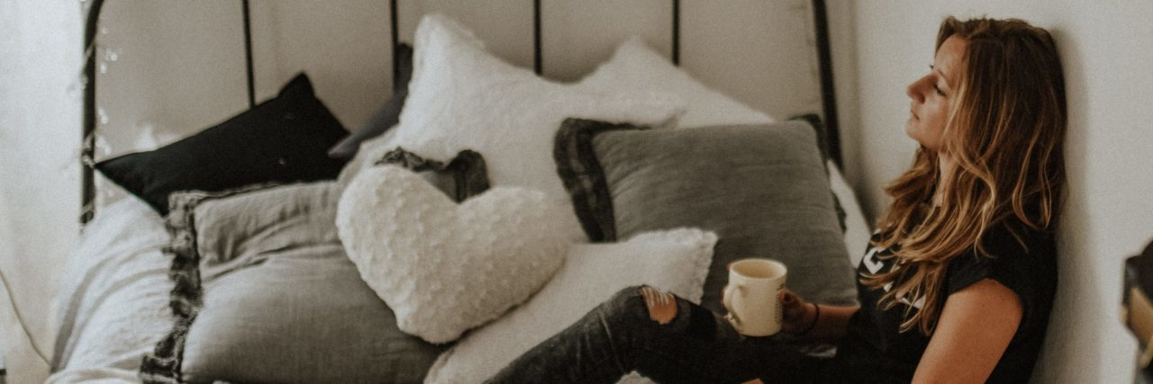 tired woman sitting on bed with cup of coffee