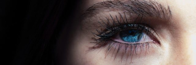 a woman whose blue eye is illuminated by light