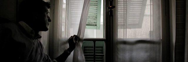 man wearing glasses in dark room and peeking through curtain