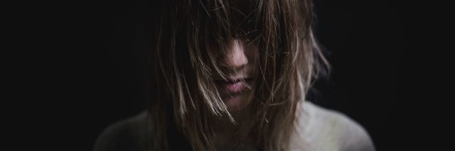young woman in darkness with hair covering eyes looking down