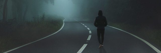 man walking along road in thick fog bordered by trees