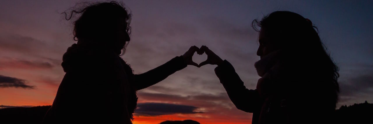 Two friends holding up their hands making a heart