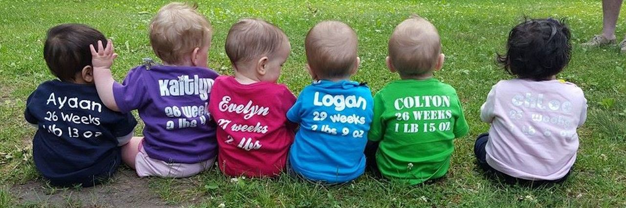 Back of 6 babies with t-shirts showing their name, when they were born and how much they weighed as preemies