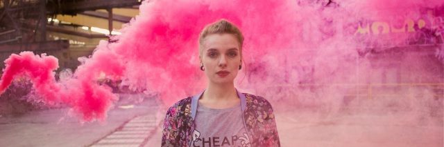 woman standing in front of a cloud of pink smoke