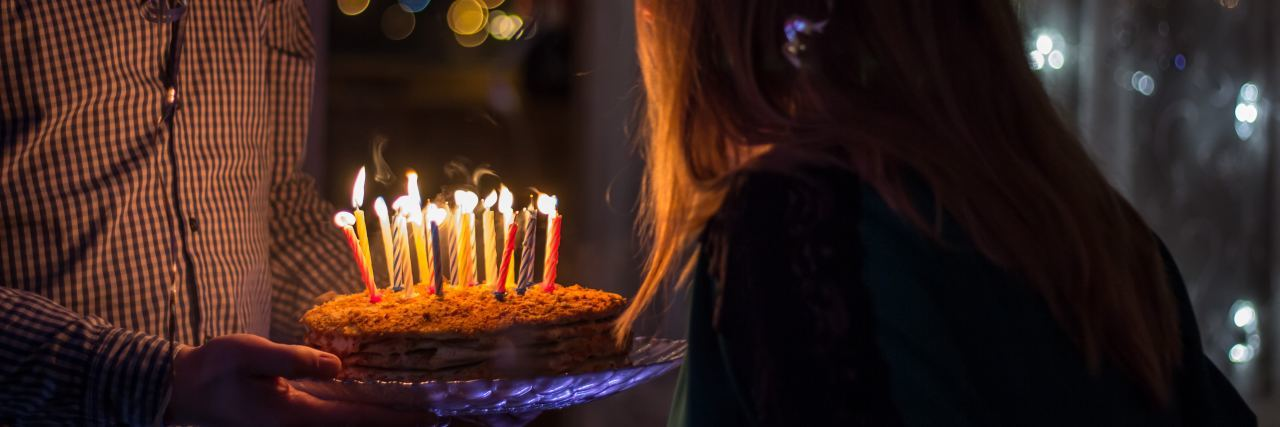 woman blowing out birthday candles on cake held by man