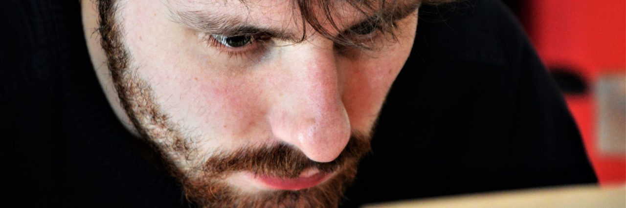 sad depressed man with beard looking closely at laptop