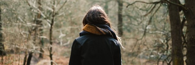 girl with a coat and scarf standing in the woods