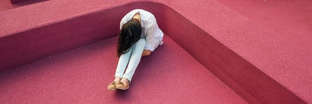 a woman sits on a pink floor hugging her legs to her chest