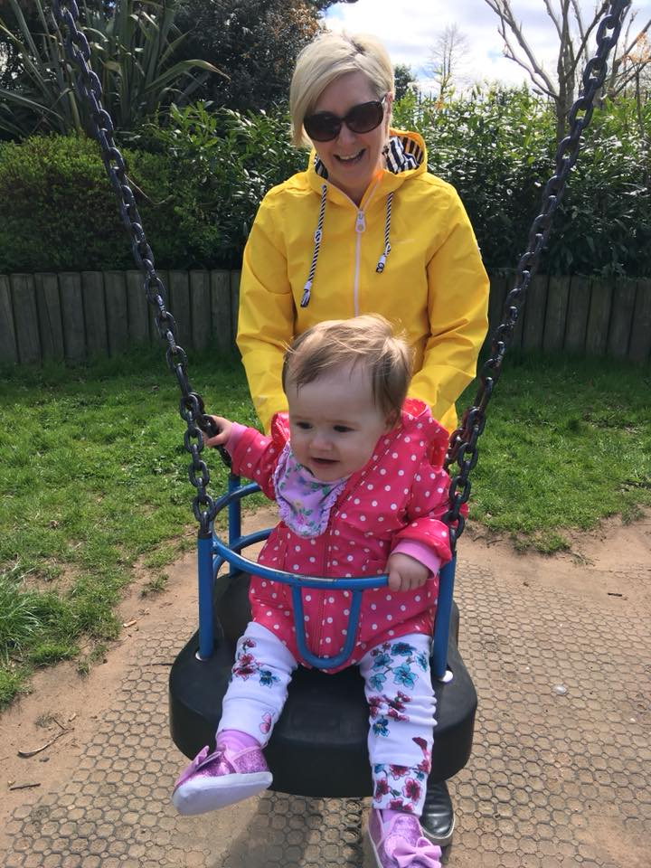 woman pushing her baby daughter in a swing