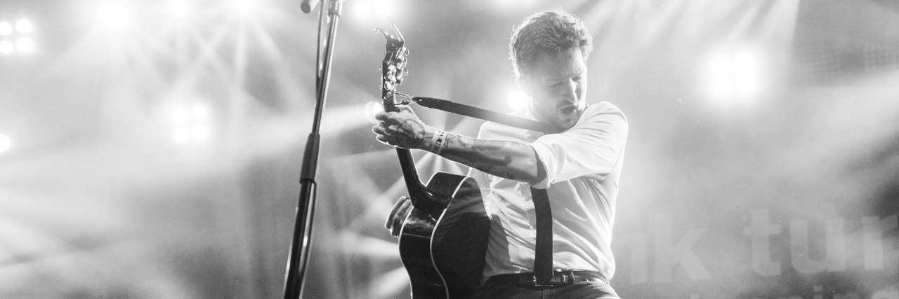 Frank Turner rocking out on guitar at a concert.