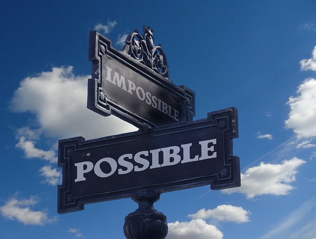 """a street sign saying """"impossible"""" crossing with another street sign saying """"possible"""""""