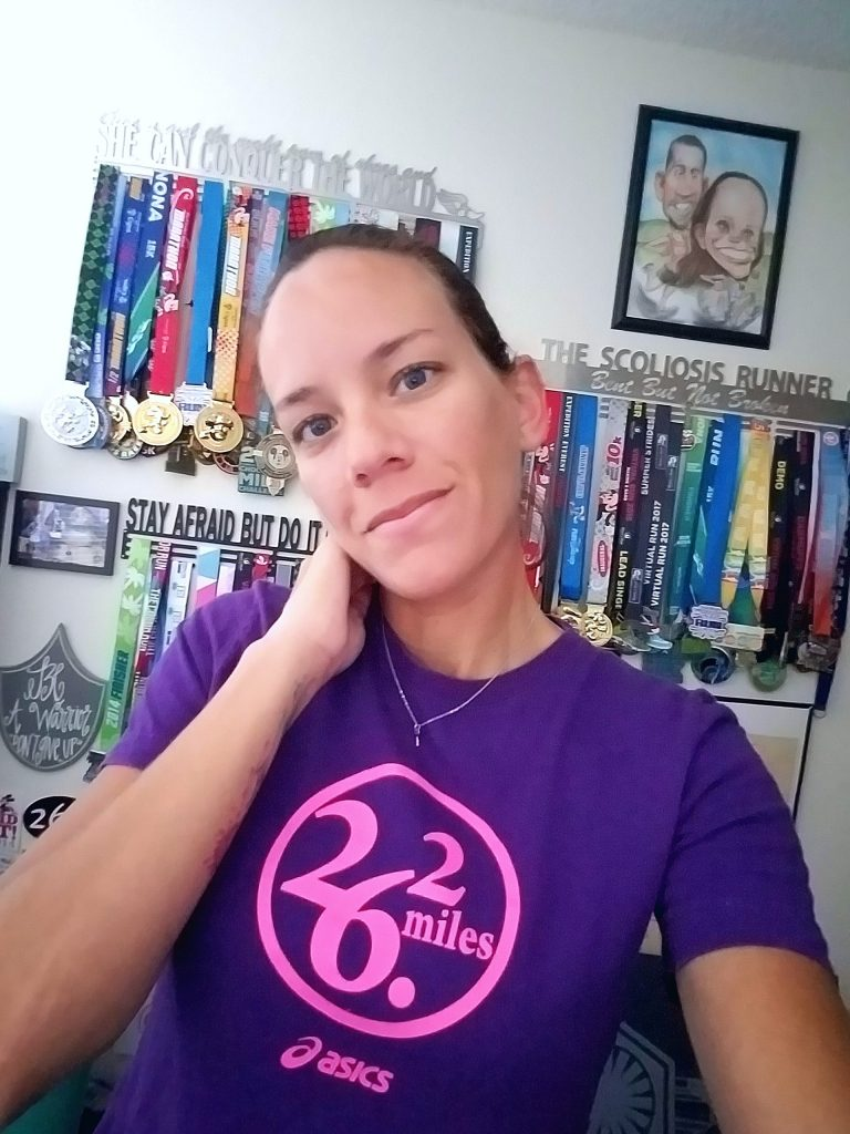 the author wearing her purple 26.2 shirt and standing in front of a wall of medals