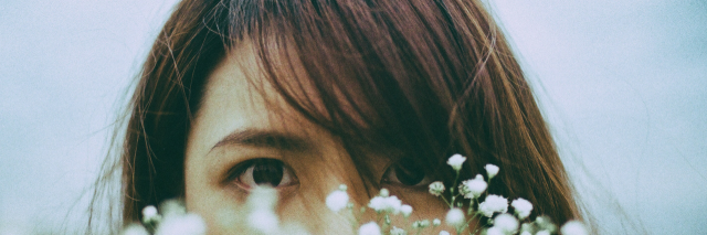 asian woman hiding behind flowers with eyes looking out over flowers