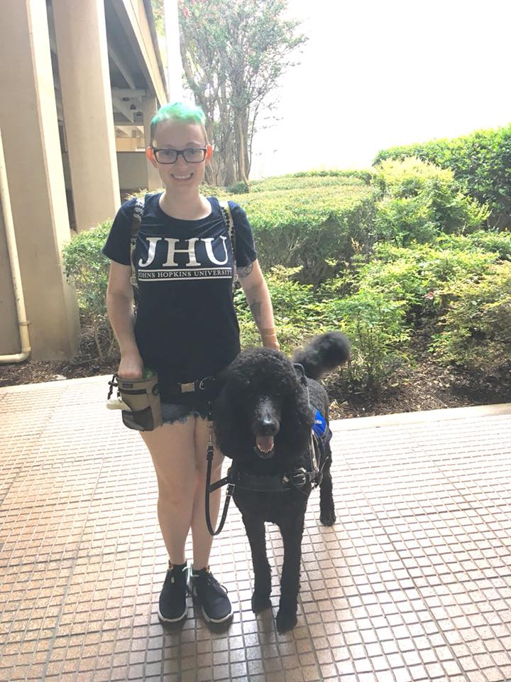 woman with blue hair standing with her service dog