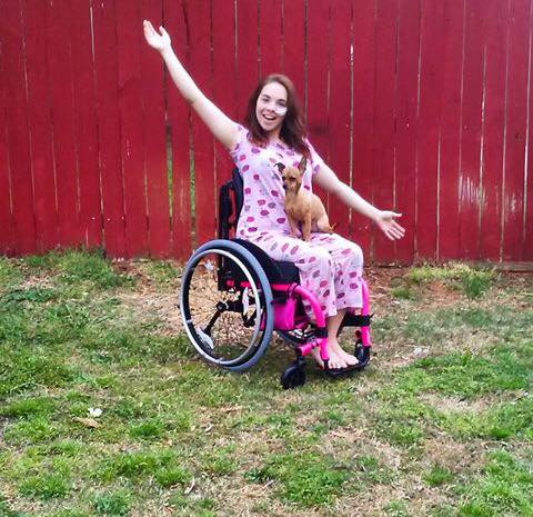 woman sitting in a wheelchair in her yard waving her arms