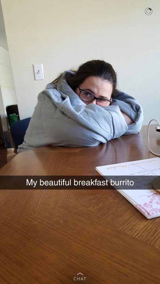 woman sitting at a table holding a blue blanket around her with the caption 'my beautiful breakfast burrito'