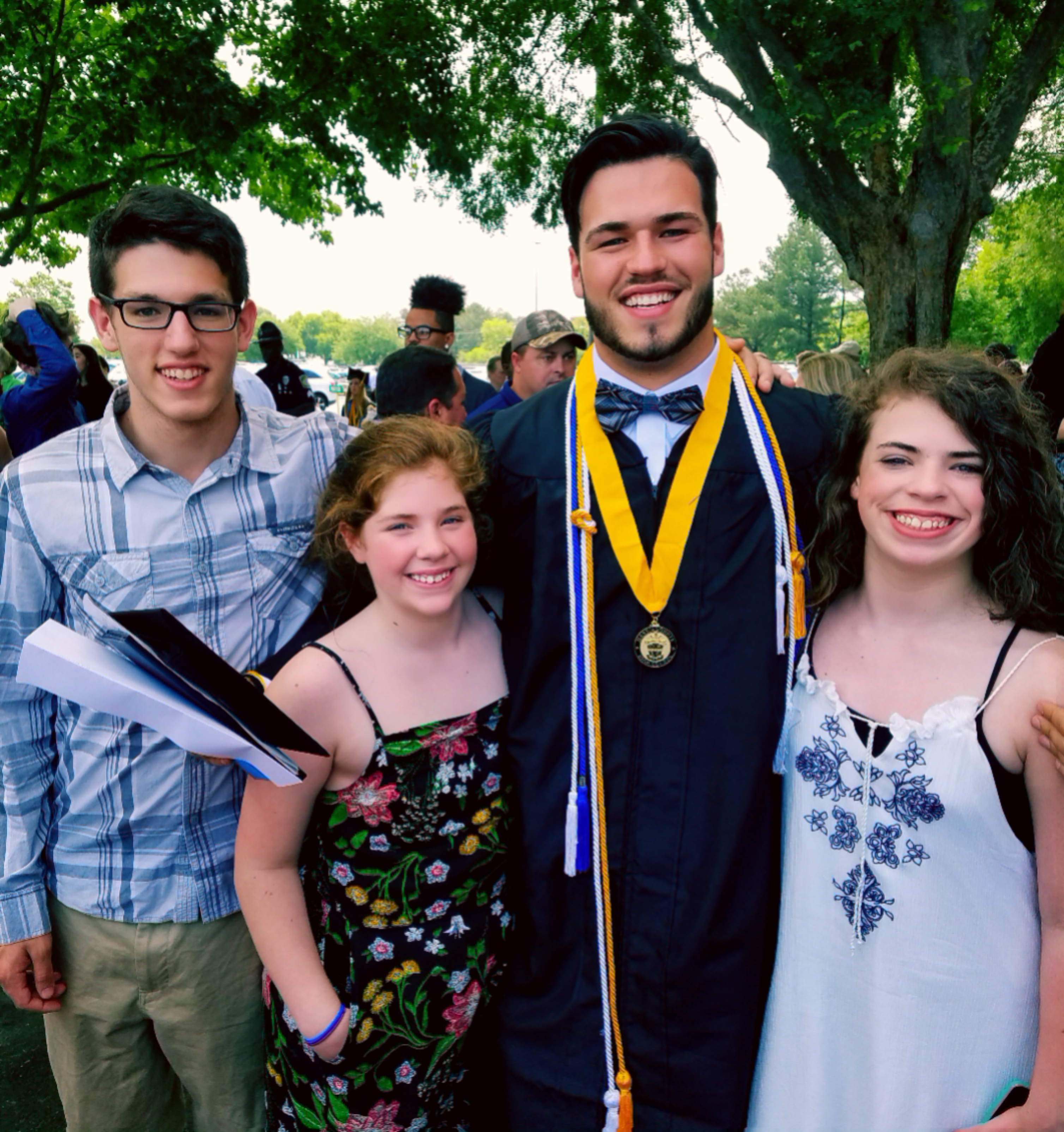A photo of the writer's four children, one wearing a graduation robe.
